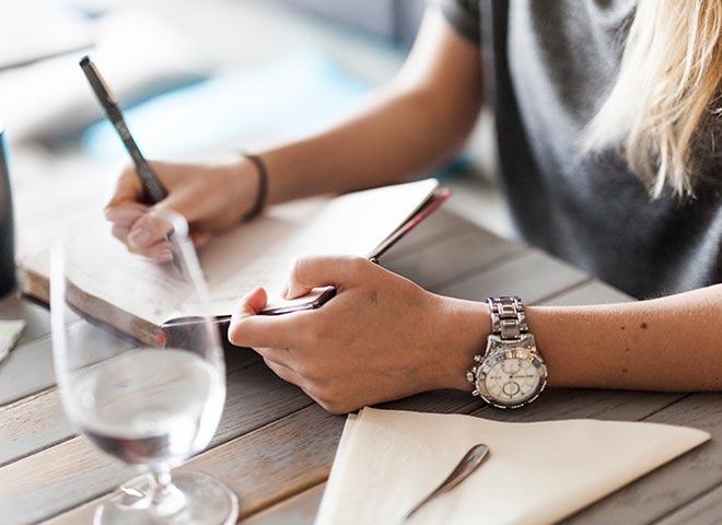writing coaching woman writing in notebook